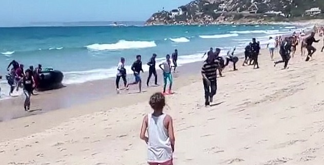 Surreal Video: Boatload Of Migrants STORM Beach Filled With Horrified Tourists
