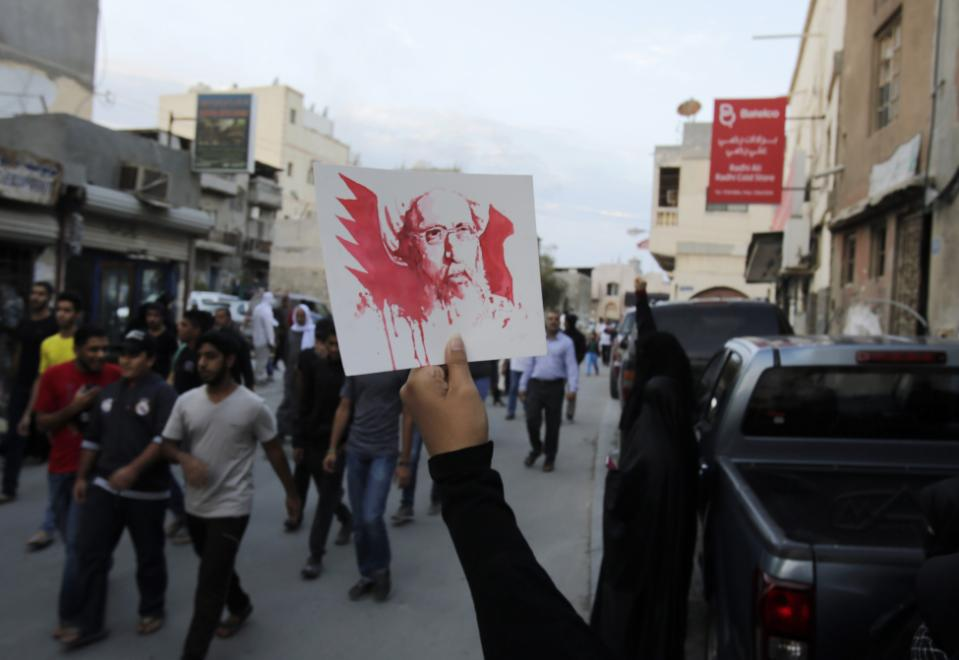 A Bahraini anti-government protester holds up a picture of Saudi Shiite cleric Sheikh Nimr al-Nimr, whose execution in Saudi Arabia was announced Saturday, during a peaceful demonstration in Daih, Bahrain, Saturday, Jan. 2, 2016. Saudi Arabia announced Saturday it had executed 47 prisoners convicted of terrorism charges, including al-Qaida detainees and al-Nimr, who rallied protests against the Saudi government. The execution of al-Nimr is expected to deepen discontent among Saudi Arabia's Shiite minority and heighten sectarian tensions across the region. (AP Photo/Hasan Jamali)